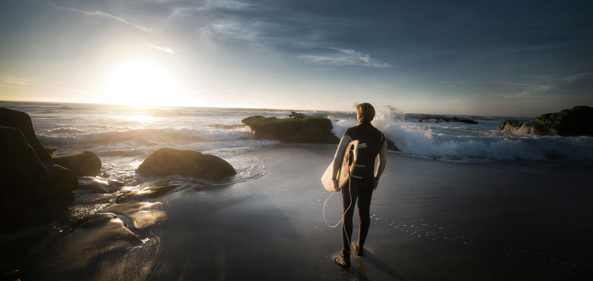 Man with surfboard looks at the ocean
