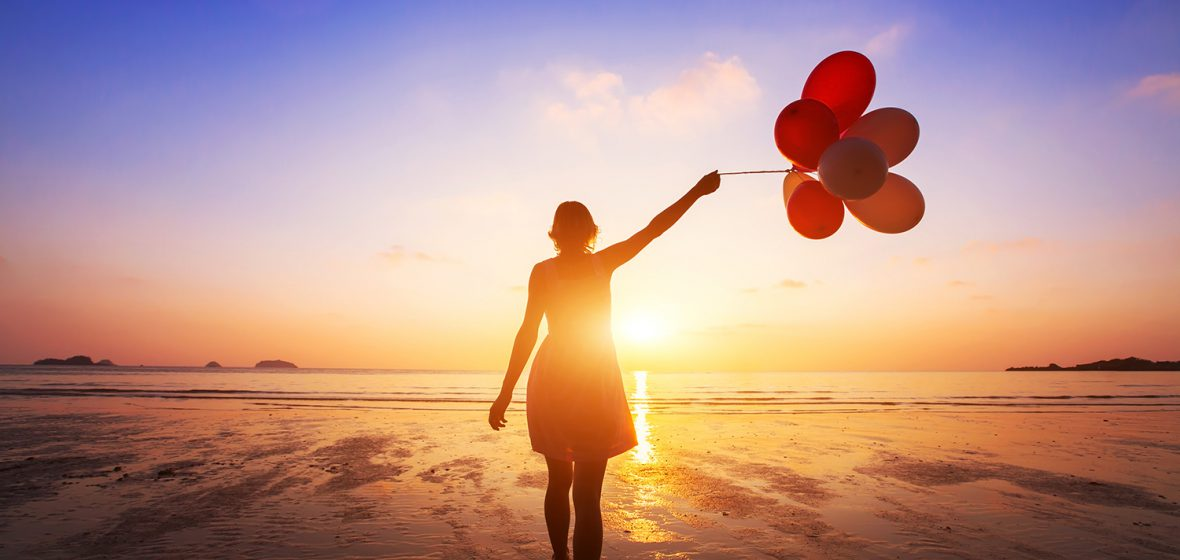 happy girl with multicolored balloons enjoying summer beach at sunset
