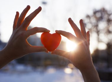 Woman holding heart-shaped snowball