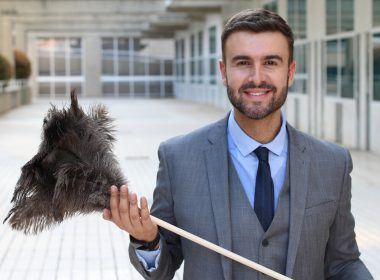 Businessman holding a feather duster.