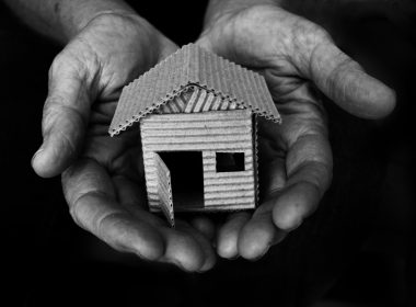 Hands holding small cardboard house