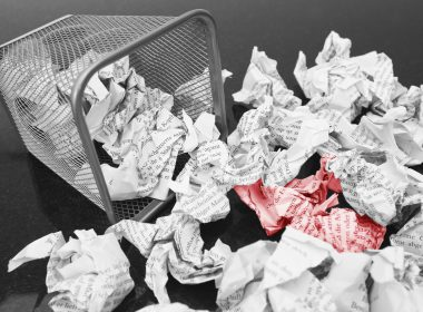 A lot of wrinkled paper laying in and around a wastepaper basket