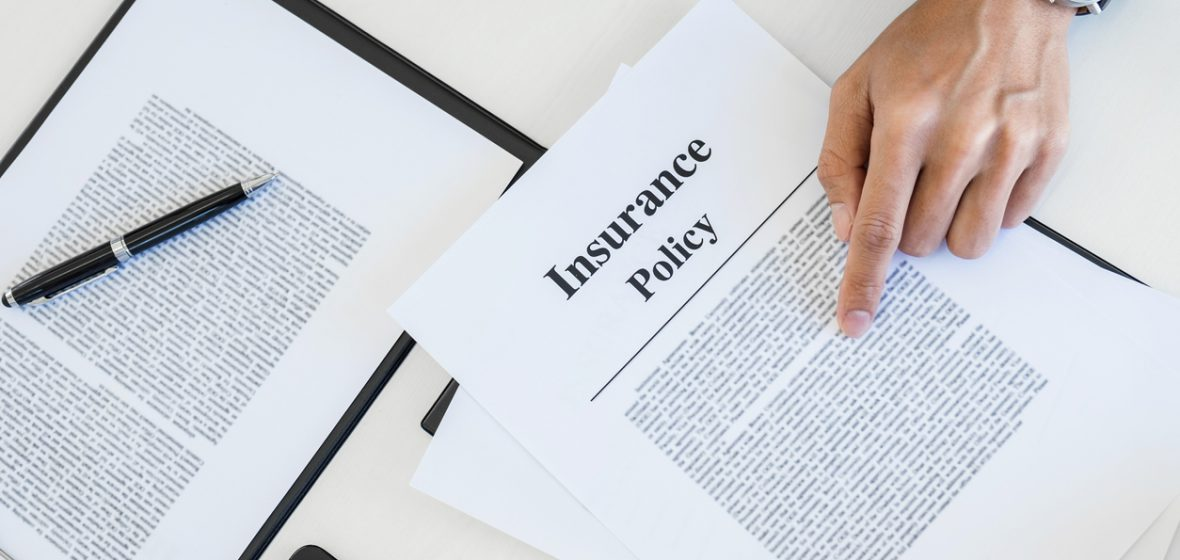 A man reviews insurance policy documents on a desk