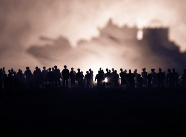 Silhouettes of a crowd standing at a border